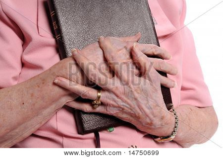 Hands of elderly woman holding Bible isolated over white
