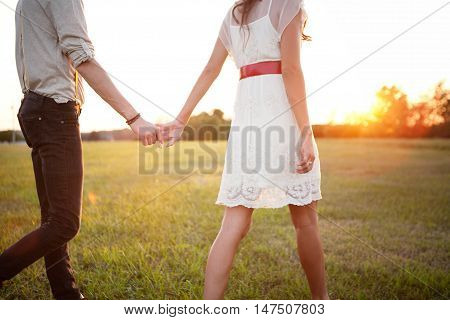 Sweet Couple Holding Hands in the field