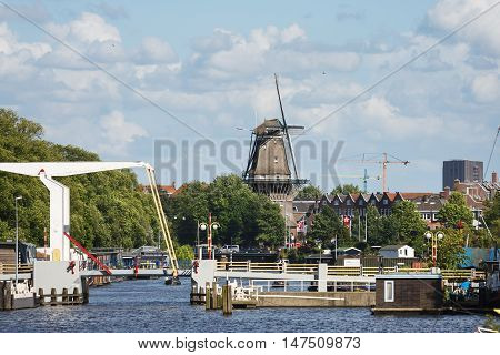 Amsterdam Netherlands - July 02 2016: The old wooden mill with drawbridge on the foreground sunny day