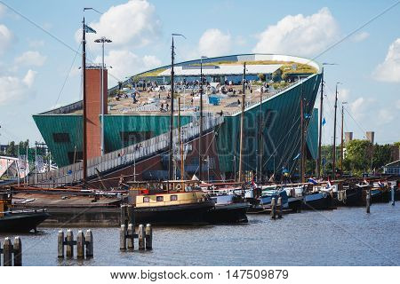 Amsterdam Netherlands - July 02 2016: Some people visit of NEMO Science museum view from Oosterdok street sunny day