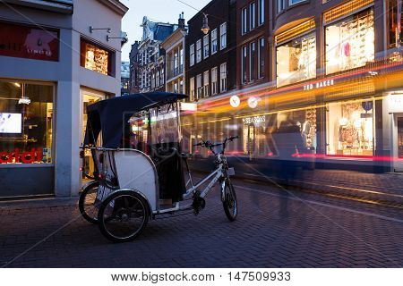 Amsterdam Netherlands - July 02 2016: Bike rickshaw awaits passengers in the night city street