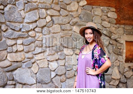 Beautiful young girl with long hear, wearing a hat, standing near a rock wall outdoors