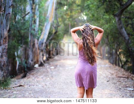 Girl walking off into the distance on a dirt road