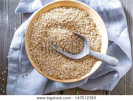 Raw Organic Steel Cut Oats in a wooden Bowl on Wood Background. Selective Focus, Toning.