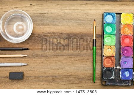 Workstation concept top view : Water color,brush,pen,marker,pencil,rubber,sharpener,glass of water and color pencil on wooden background