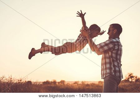 Father and son playing in the park at the sunset time.Family having fun on the field. Concept of friendly family and of summer vacation.