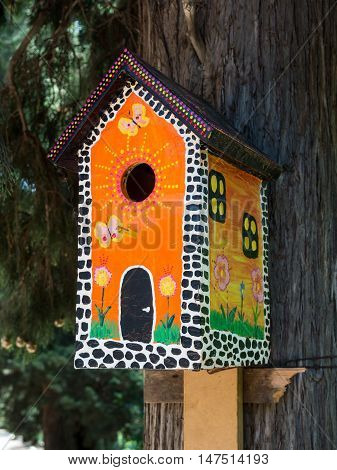 Bright painted under the multi-storey house birdhouse on a tree trunk