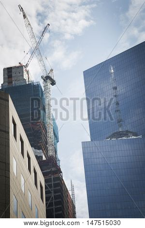 NEW YORK - SEPT 9 2016: Reflection of the Freedom Tower on the glass of Tower 4 at World Trade Center site and Tower 3 under construction the weekend of the 15th anniversary of the terrorist attacks.