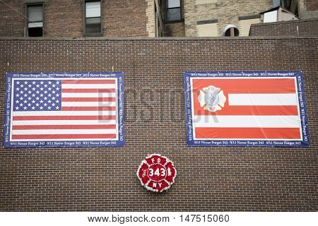 NEW YORK - SEPT 9 2016: Wreath of red flowers shaped as FDNY badge and banners above the Memorial Wall at the FDNY Ten House fire station before the 15th anniversary of the terror attack at the WTC.