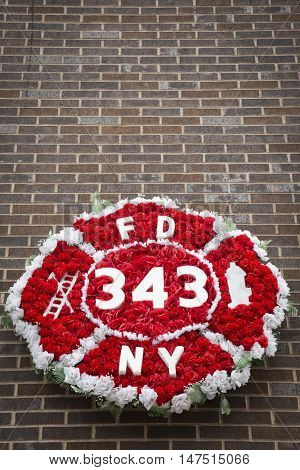 NEW YORK - SEPT 9 2016: Wreath of red flowers shaped as FDNY badge and 343 for the firefighters killed on Sept 11 displayed at Ten House fire station before the 15th anniversary of the terror attack.
