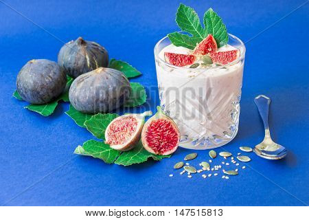 Glass of yogurt with pieces of fig fruit near scattered seeds laid ripe fig fruits on the fig tree leaves spoon on the blue background. Glass of yogurt with fig fruit slices. Horizontal. Daylight.