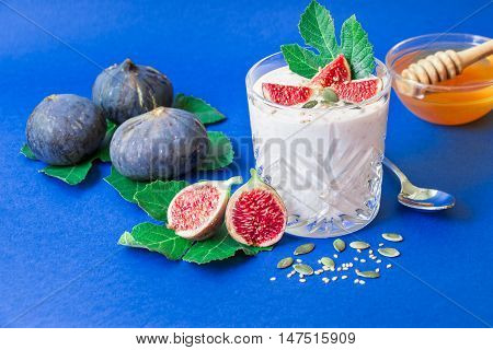 A glass of yogurt with pieces of fig fruit near scattered seeds laid ripe fig fruits spoon honey on the blue background. A glass of yogurt with fig fruit slices and honey. Horizontal. Daylight.