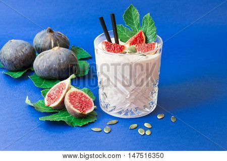 Glass of fig fruit smoothie fig slices straws and near scattered sunflower seeds ripe fig fruits on the fig tree leaves on the blue background. Fig fruit smoothie glass. Horizontal. Daylight.