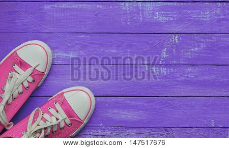 pair of pink sneakers on purple worn wooden background top view