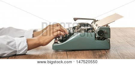 Man working on retro typewriter at desk on white background