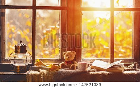 fall. cozy window with autumn leaves a book a mug of tea