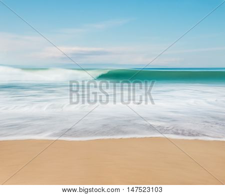 An ocean wave breaking along the coast of California. Image features motion blur from a long exposure and camera panning.