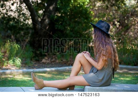 Girl in shorts and a black hat in a garden in the shade
