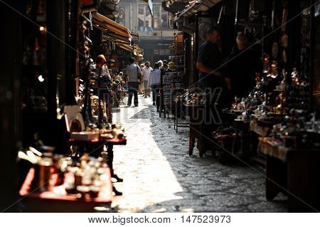 BOSNIA SARAJEVO - AUGUST 27 2015: Tourists looking at souvenirs in old Sarajevo bazaar on August 27 2015 in Sarajevo.