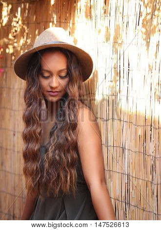 Girl with beautiful long hair and a hat against a bamboo fence