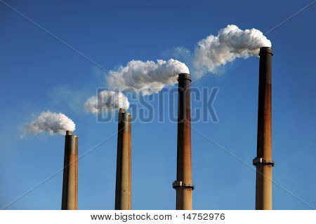 Industrial smokestacks with smoke clouds over blue sky