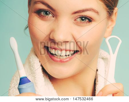 Pretty young girl with electric brush and tongue cleaner. Happy woman cleaning her oral cavity caring about dental health.