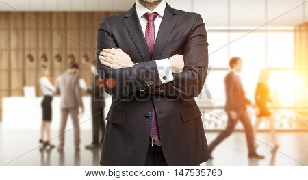 Torso of businessman in suit standing in busy office of consulting company. Concept of charismatic leader. Toned image