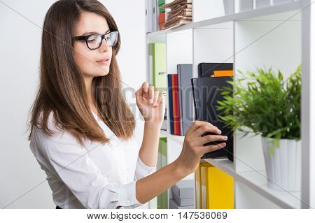 Young business lady wearing glasses is taking a black book from shelf in office. Concept of legal work and reading a lot