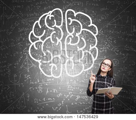 Nerd girl in dress standing with her book near blackboard with formulas and giant brain sketch on it. Concept of critical thinking