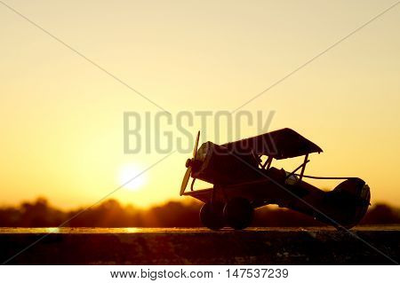 sunset silhouette of an old bi plane