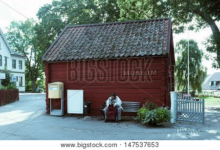 SIGTUNA, SWEDEN - SEPTEMBER 5TH, 2015: Old lady sits on the bench in front of a little museum in a small town called Sigtuna, Sweden.