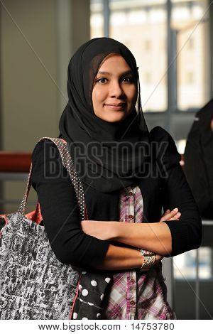 Портрет молодой мусульманской женщины руками скрещенными