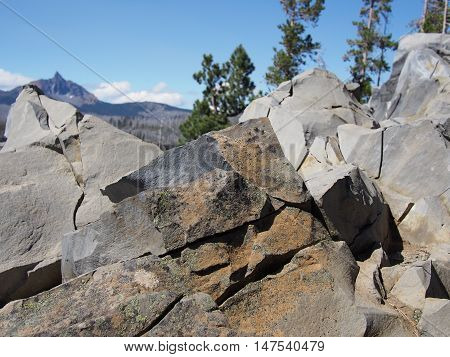 Close up of jagged boulders and their details with Mt. Washington in Oregon's Cascade Mountain Range in the distant background.