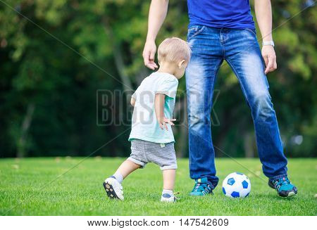 Young man and toddler son playing football in park