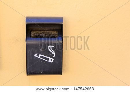 Dirty ash tray bin outside mounted on stucco plaster wall with copy space