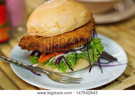 vegetarian burger made from vegetables and breadcrumbs, stacked with onion rings