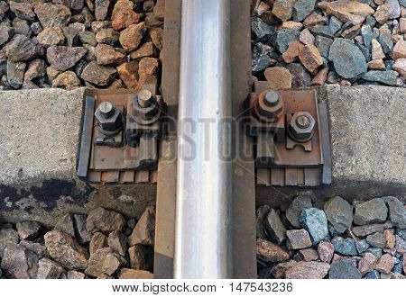Fragment of railway rail and cross tie close up on embankment from gravel. Top view.