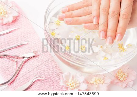 Beautiful woman's hands with manicure in bowl of water. Studio shot