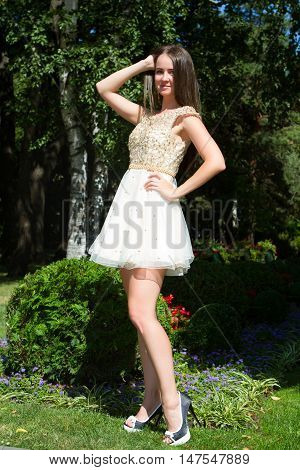 beautiful young girl with brown hair in a bright dress is walking in a summer park