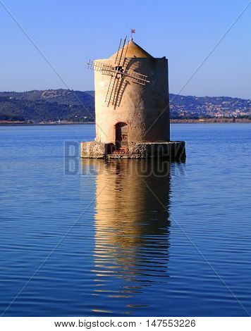 Old slanted windmill in water Orbetello Italy