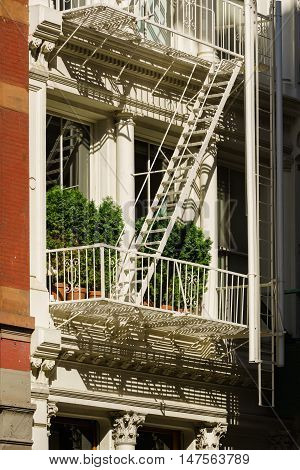 Close up of building with fire escape and trees. Soho, Manhattan, New York City