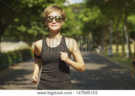 Young Chinese woman jogging in city park in the morning