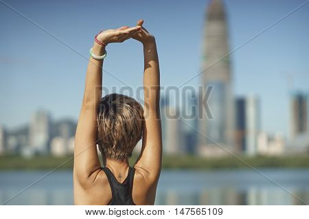 Chinese young woman doing stretch after jogging
