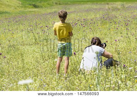 CASTELLUCCIO,ITALY-JULY 9,2016:Woman and child look and take photograf of multicolored flower meadows on the plateau of Castelluccio during a summer day.