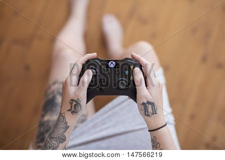 Gothenburg, Sweden - September 17, 2016: A close up shot from above of a tattooed young woman's hands holding a black Xbox One controller as she is playing a video game.