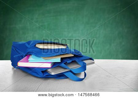 Blue backpack with school supplies on wooden table against blurred chalkboard background. School concept.