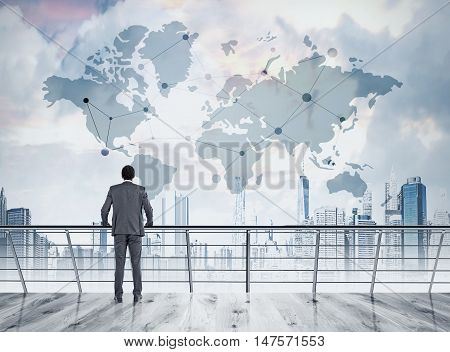 African American businessman is standing on his office balcony and looking at large world map in the sky. Concept of hallucinations and international trade