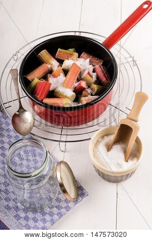 preparation of home made rhubarb jam in a red enamel pot with preserving sugar