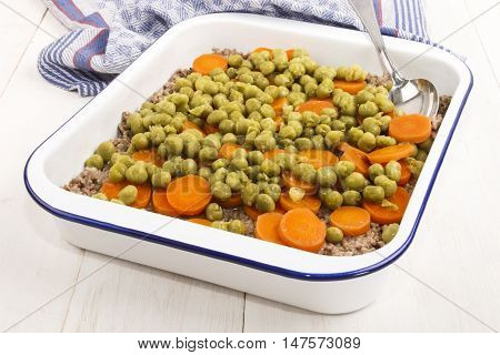 shepherd's pie in baking enamel roaster with minced meat sliced carrot and mushy pea