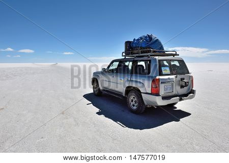 SALAR DE UYUNI - AUGUST 28: Off-road car on surface of lake Salar de Uyuni in Bolivia on August 28 2016. Salar de Uyuni is the worlds largest salt flat at 10582 square kilometers
